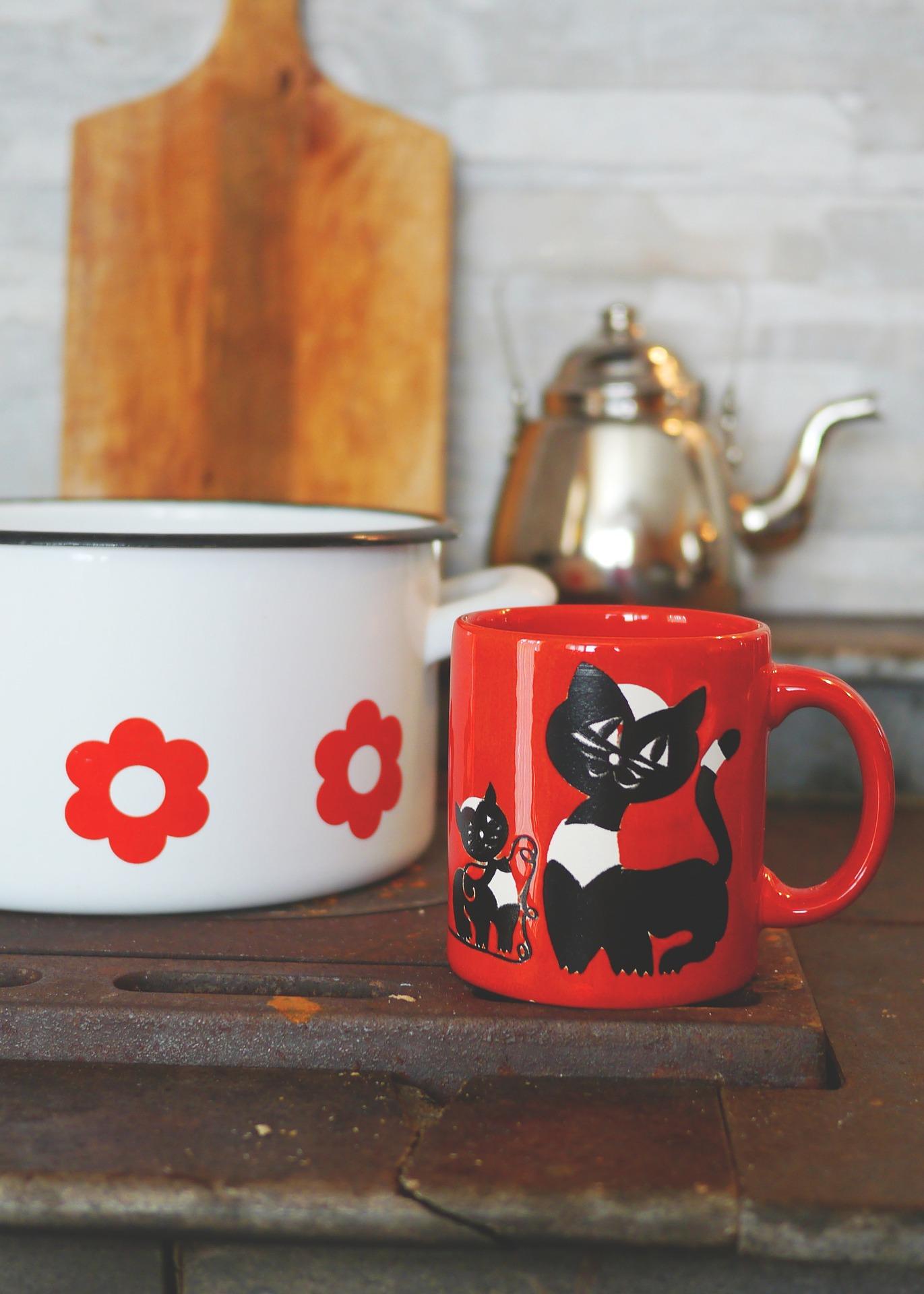 Emaliowany garnek i kubek czerwony z kotem.